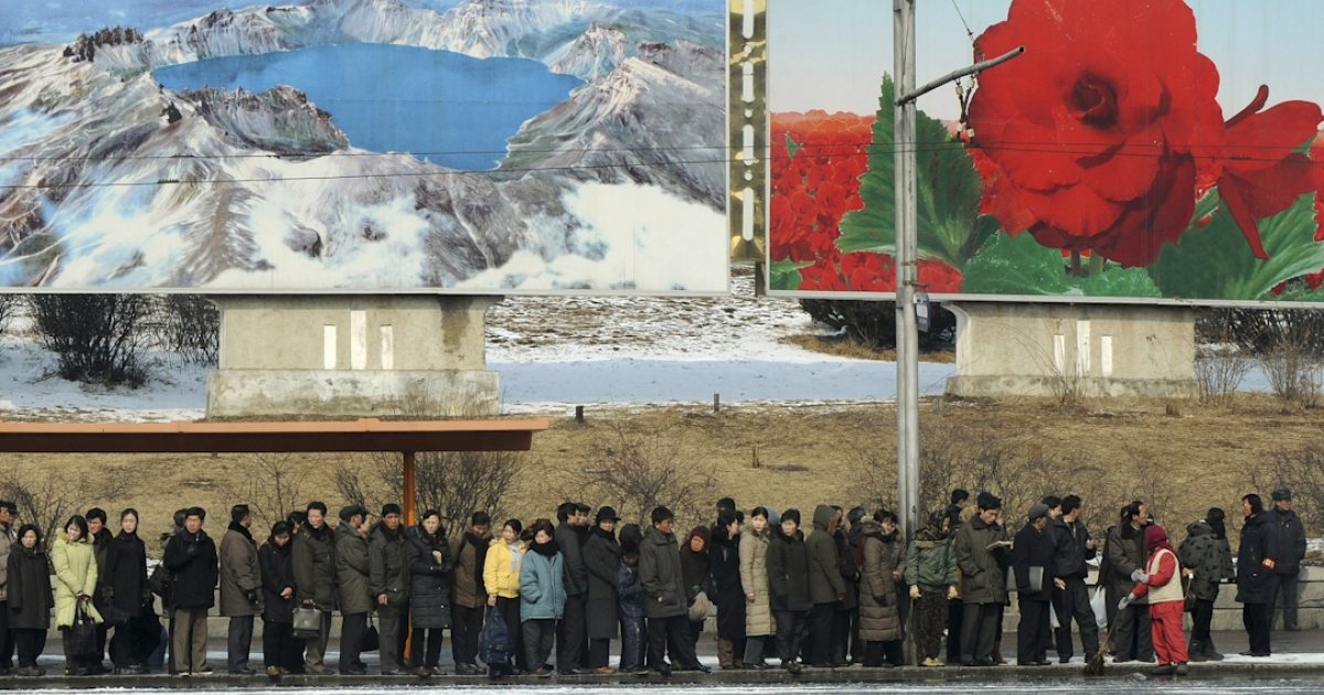 North Korean commuters wait for a bus beneath posters showing Mount Paekdu and the Kim Jong-Il flower in the North Korea capital, Pyongyang.</p>