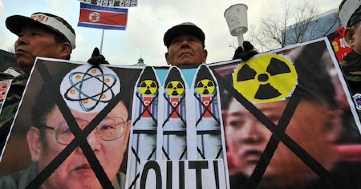 A South Korean veteran holds a placard showing North Korean flags and portraits of Kim Jong-Il (L) and his son Jong-Un (R) during a rally in Seoul.</p>