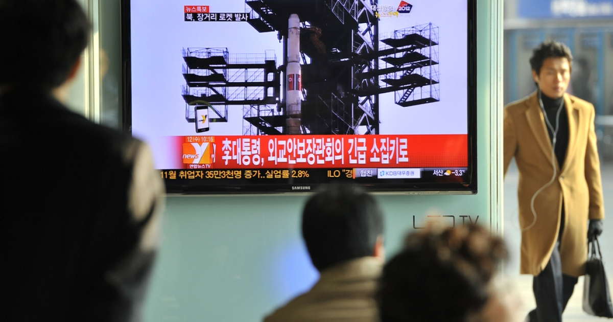 Travellers watch a TV screen broadcasting news on North Korea's rocket launch, at a railway station in Seoul on December 12, 2012. North Korea on December 12 launched a long-range rocket which Japanese authorities said passed over its southern island chain of Okinawa. It was the second launch this year, after a failed attempt in April.</p>