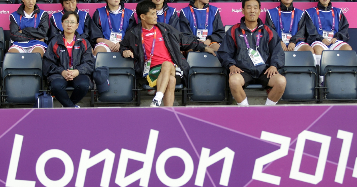 North Korea's coach Gun Sin Ui (C) waits for his team's delayed group G women's match against Colombia to start in the football competition in the London 2012 Olympic Games at Hampden Park, Glasgow, Scotland, on July 25, 2012.</p>