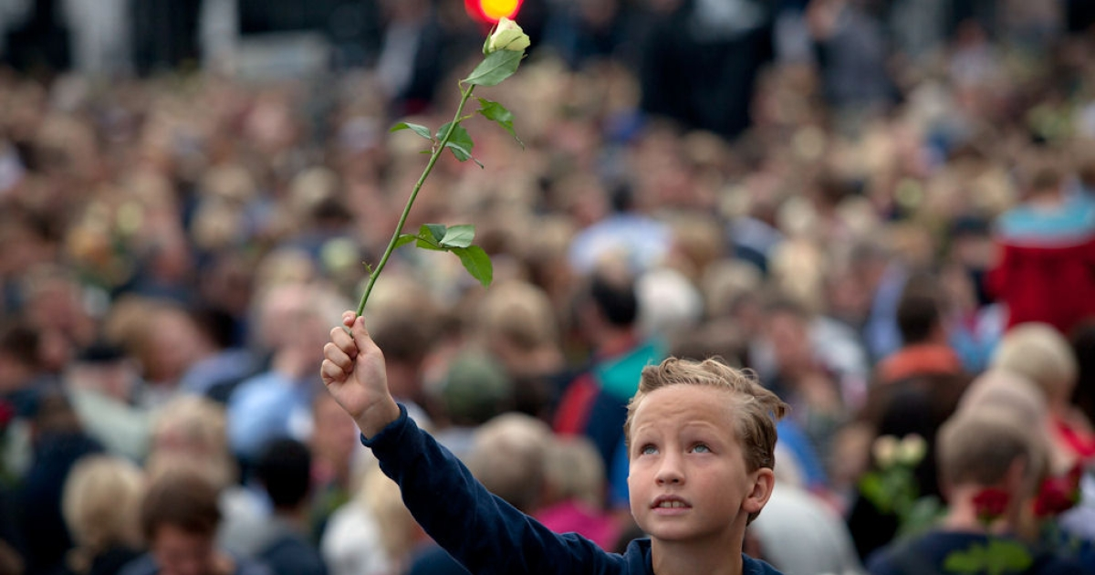 A boy holds a rose as hundreds of thousands of people gathered at a memorial vigil on July 25, 2011 in Oslo, Norway following attacks July 22 in Oslo and on Utoya Island.</p>