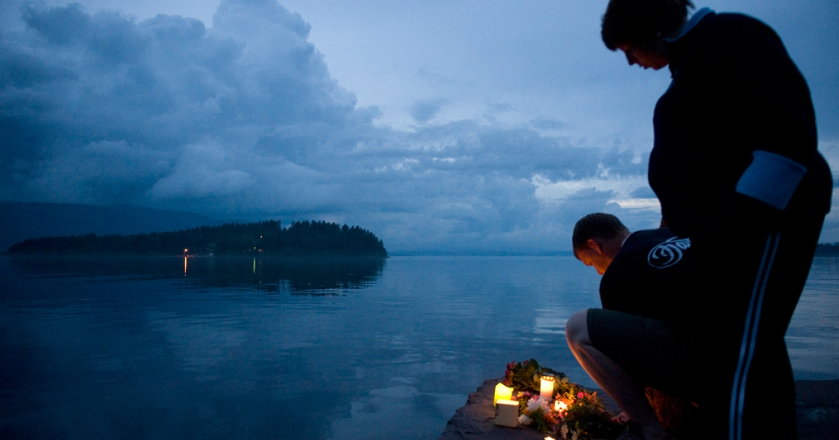 The Utoeya island, 40km south west of Oslo is seen in the background as people light candles on July 23, 2011 in memory of the victims of July 22 shooting spree on the island.</p>