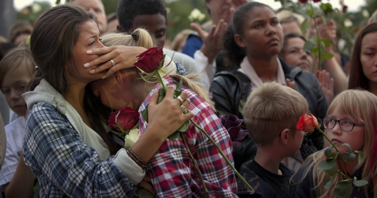 Mourners comfort each other at a memorial vigil in July, following attacks by Anders Behring Breivik.</p>