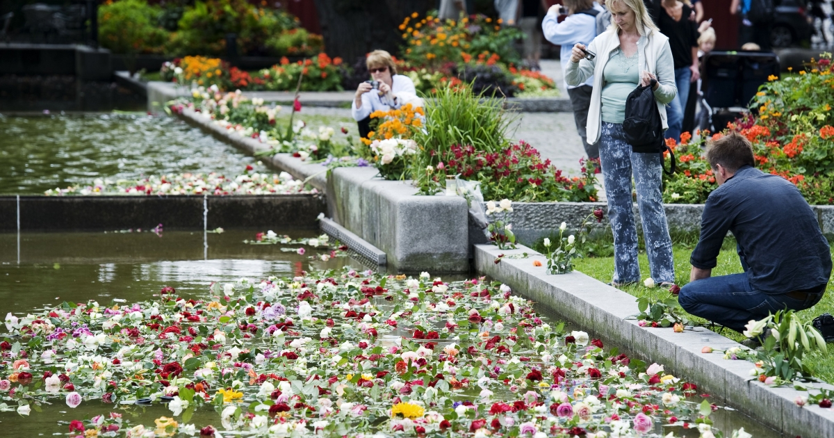 People take pictures as roses float on July 26, 2011 on water after 150,000 people gathered on Monday for a flower vigil in Oslo, in a show of solidarity with the victims of recent attacks in Norway.</p>