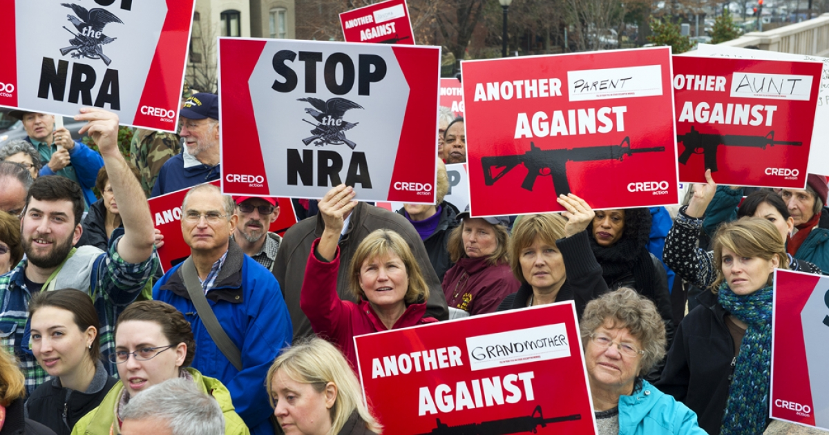 Protesters marching with the social activist group CREDO along with other concerned citizens descend on the offices of the NRA's (National Rifle Association) Capitol Hill lobbiest's office demanding the pro-gun lobby stand down in reaction to the shooting at Sandy Hook Elementary School December 17, 2012, in Washington, DC.</p>