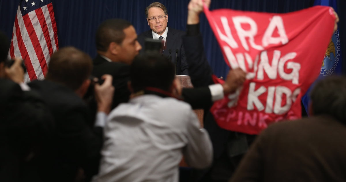 A demonstrator from CodePink holds up a banner as National Rifle Association Executive Vice President Wayne LaPierre delivers remarks during a news conference at the Willard Hotel December 21, 2012 in Washington, DC. This is the first public appearance that leaders of the gun rights group have made since a 20-year-old man used a popular assault-style rifle to slaughter 20 school children and six adults at Sandy Hook Elementary School in Newtown, Connecticut, one week ago.</p>