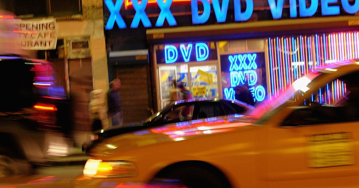 Taxi cabs pass an adult video store in Times Square.</p>
