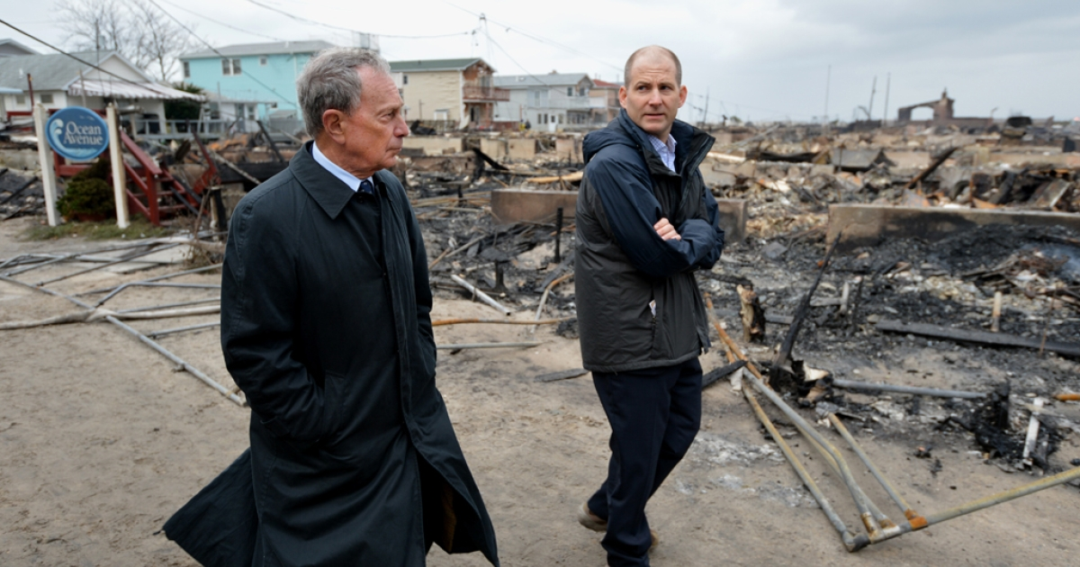 New York City Mayor Michael Bloomberg (L) views damage in the Breezy Point area of Queens in New York on October 30, 2012 after fire destroyed about 80 homes as a result of Hurricane Sandy which hit the area on October 29.</p>