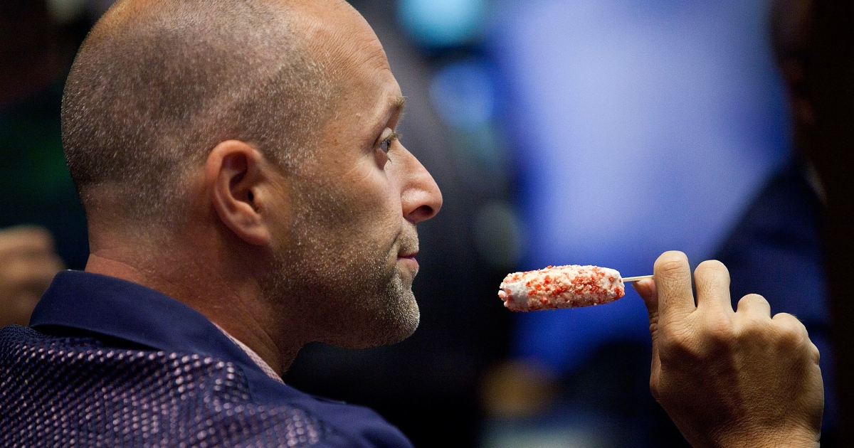 A trader enjoys a frozen treat on the floor of the New York Stock Exchange in New York City on June 29, 2012.</p>