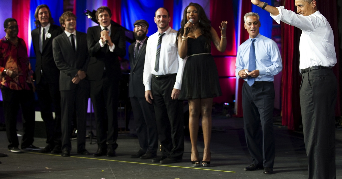 President Barack Obama (R) walks on stage at the Aragon Ballroom in Chicago, Illinios, Aug. 3, 2011, as Herbie Hancock (L), members of the band OkGo (C), Jennifer Hudson (3rd R) and Chicago Mayor Rahm Emanuel (2nd R) sing