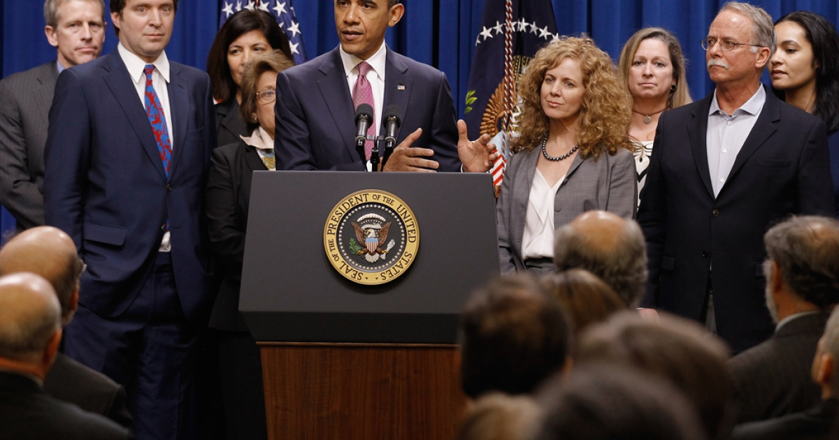 Standing with millionaires and their assistants, President Barack Obama makes a statement about the
