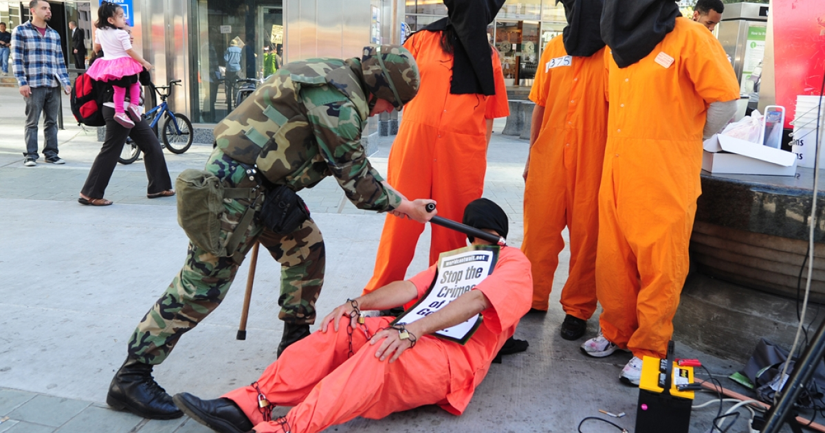 A demonstrator dressed as a Guantanamo Bay prisoner receives mock punishment from another dressed as US military personnel during a