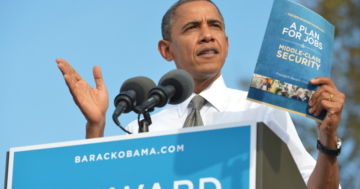 US President Barack Obama shows a copy of his jobs plan as speaks during a campaign rally October 23, 2012 at Triangle Park in Dayton, Ohio.</p>