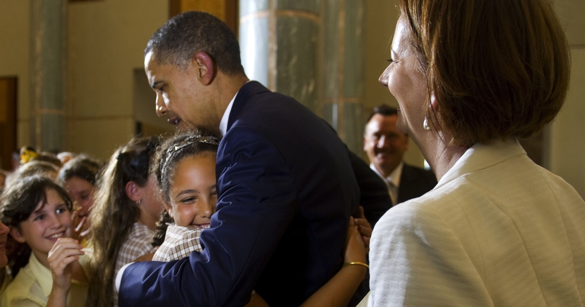 US President Barack Obama is hugged by a student as he arrives with Australian Prime Minister Julia Gillard (R) at Parliament House in Canberra on November 16, 2011.</p>