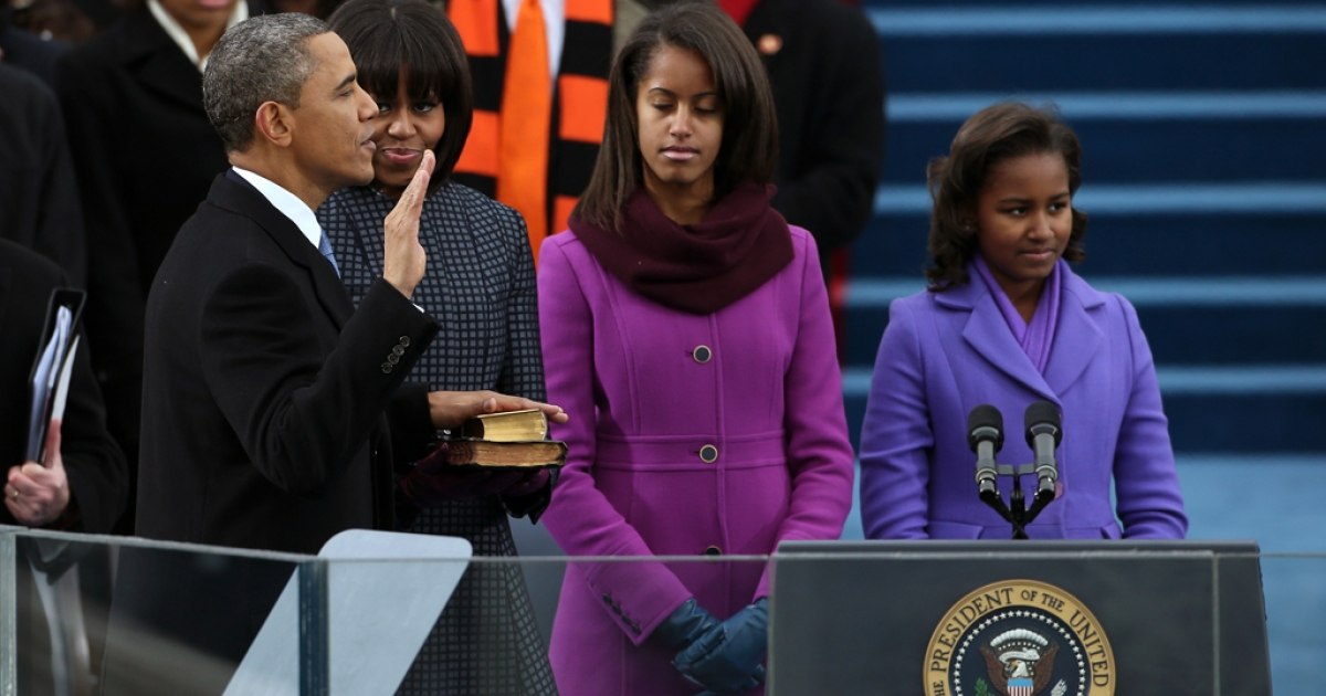 US President Barack Obama is sworn in during the public ceremony as First lady Michelle Obama, and daughters, Sasha Obama (R) and Malia Obama look on during the presidential inauguration on the West Front of the U.S. Capitol January 21, 2013 in Washington, DC. Barack Obama was re-elected for a second term as President of the United States.</p>