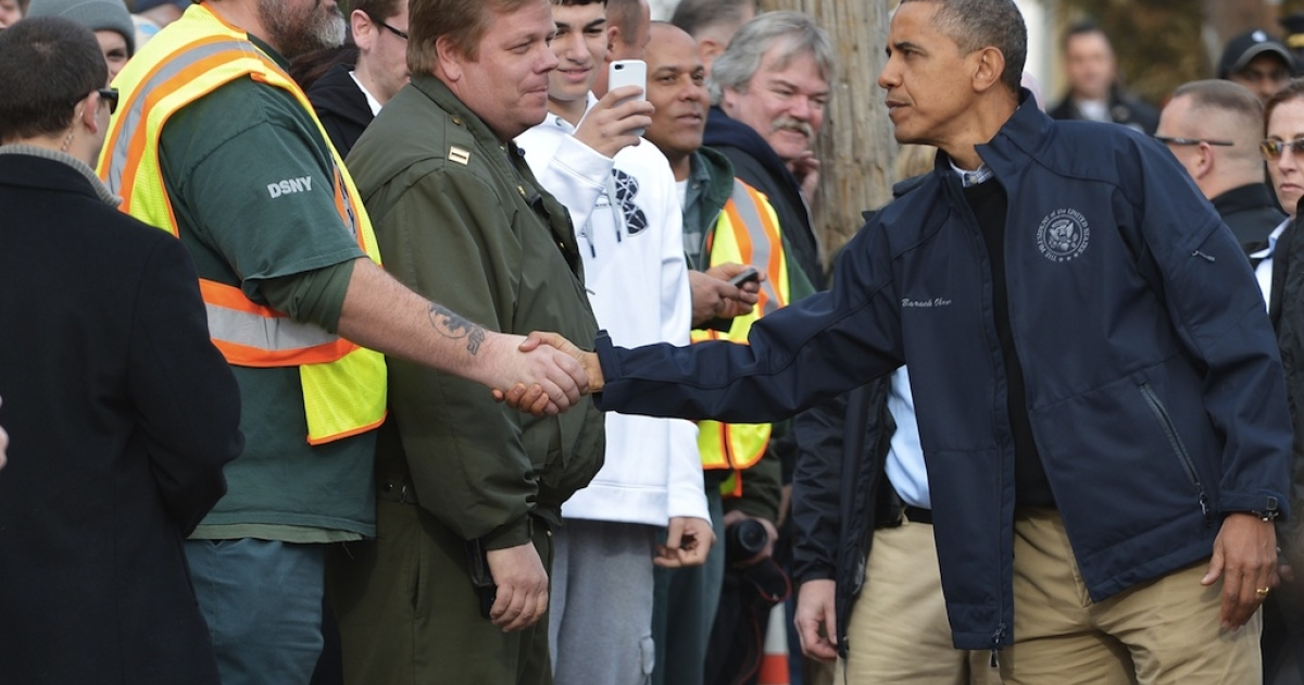 US President Barack Obama greets workers as he visits Cedar Grove Avenue on Staten Island to visit areas stricken by Hurricane Sandy in New York City on November 15, 2012.</p>