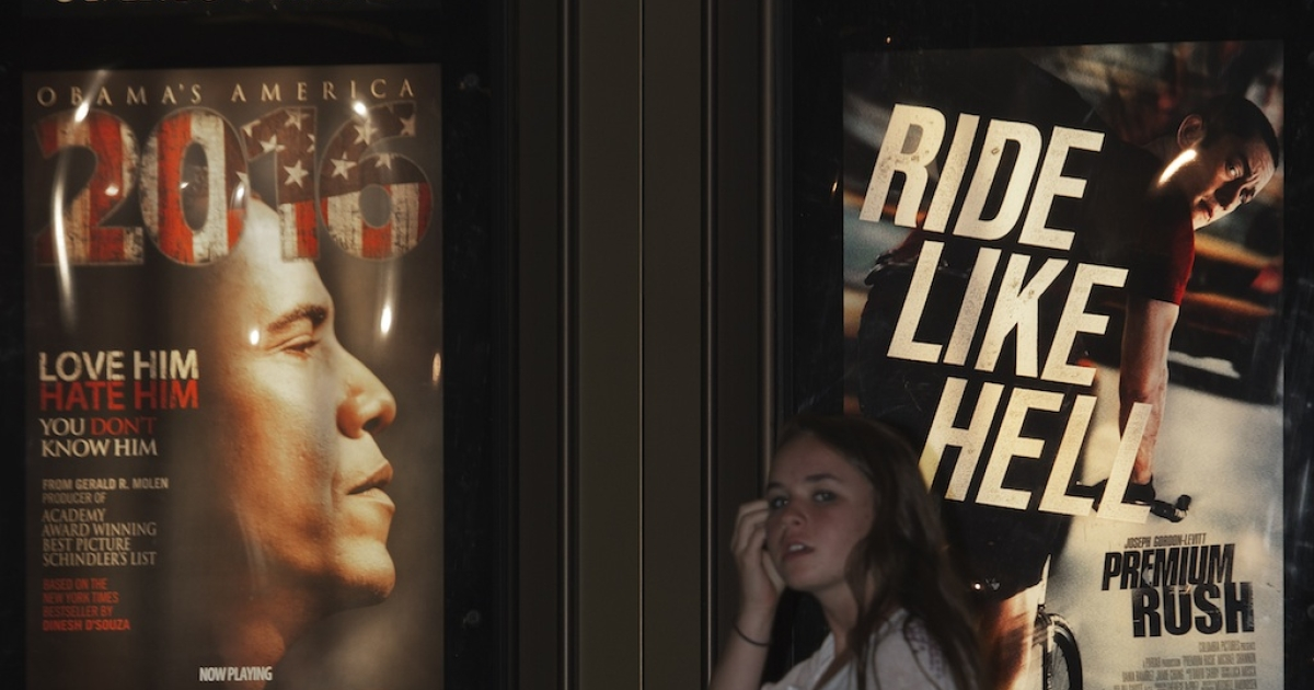 A young lady is seen walking past a promotional poster at the Rave Fairfax Corner movie theater in Fairfax, Virginia, announcing the new movie '2016: Obama's America' that opened in theaters across the US, August 24, 2012.</p>