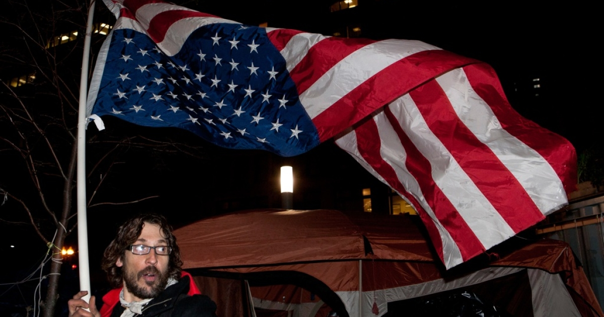 An Occupy Boston protestor carried an upside-down American flag through the Dewey Square encampment in Boston, Mass., on Dec. 8, 2011.</p>