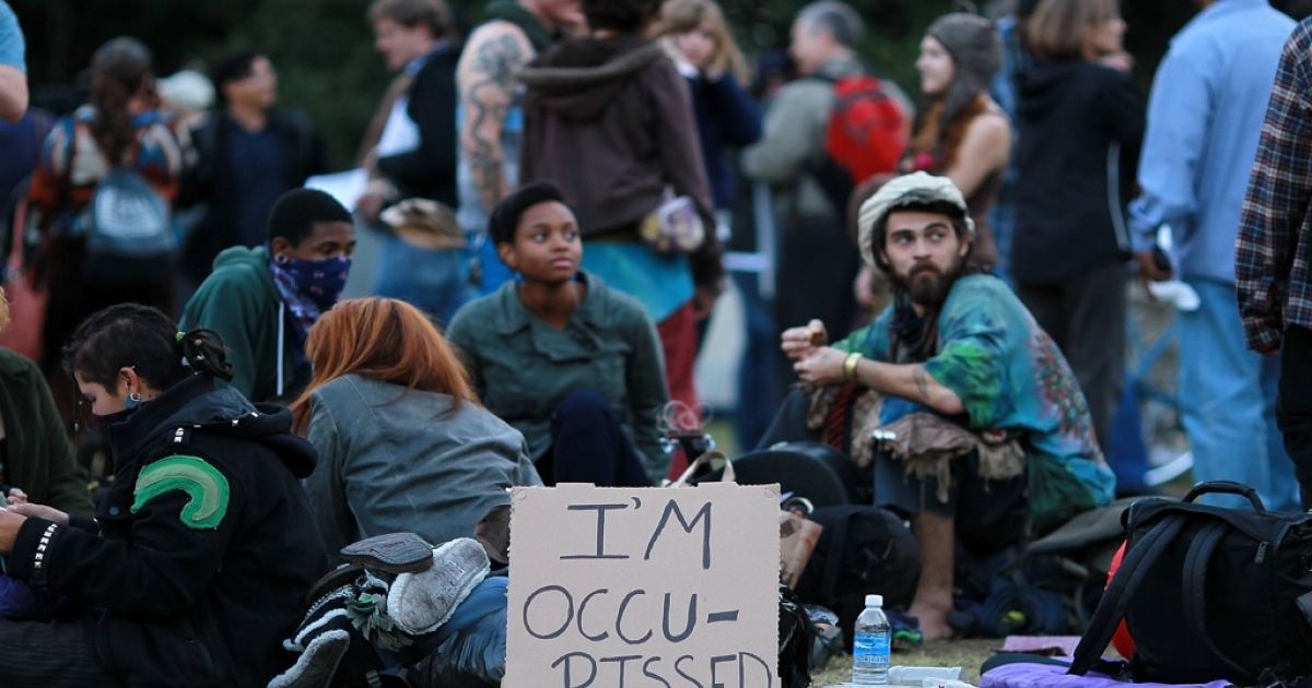 Members of Occupy Oakland sit on the grass in front of Oakland City Hall in Oakland, Calif., on Oct. 27, 2011.</p>