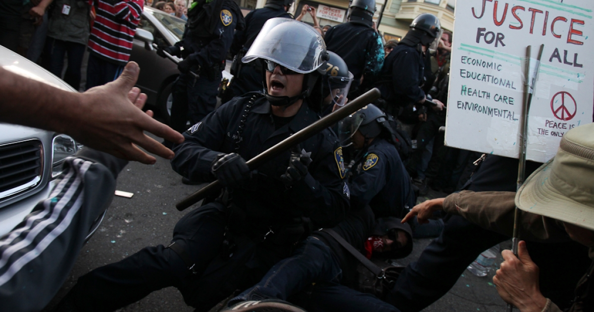 A police officer attempts to control the scene after being surrounded while making an arrest at an