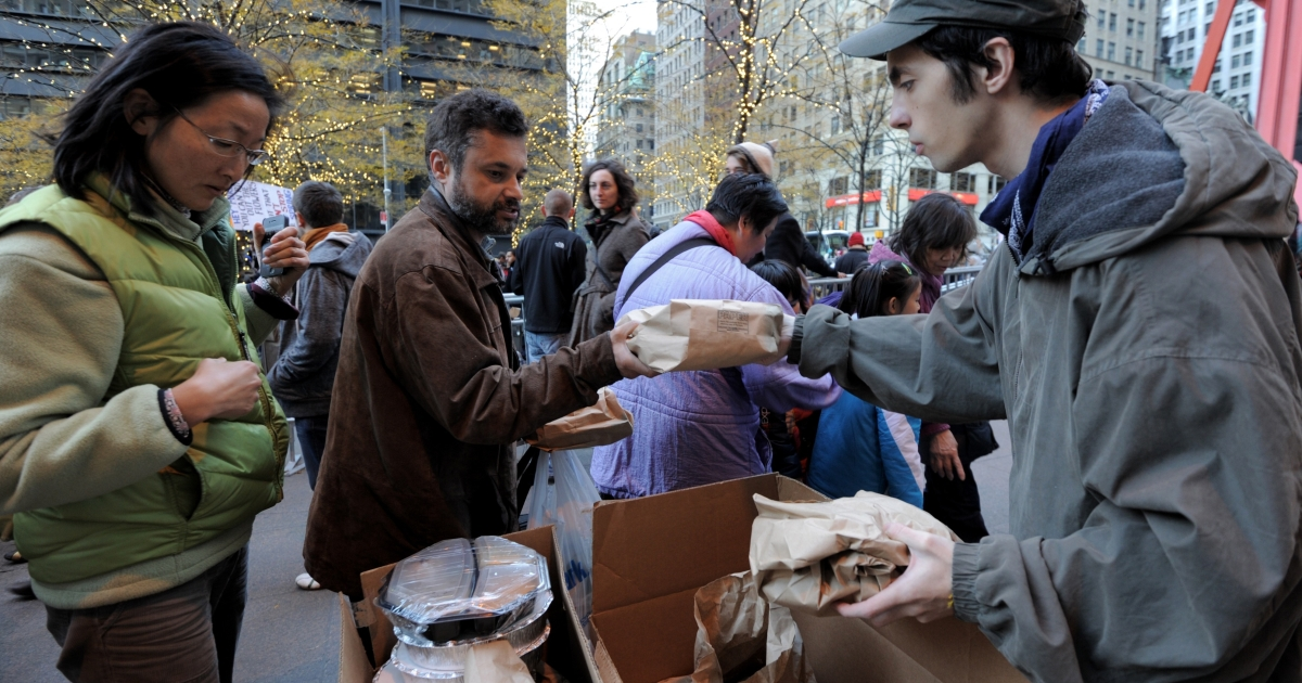A volunteer (R) hands out a packaged meal as Occupy Wall Street protesters eat donated Thanksgiving dinners in Zuccotti Park in New York City on Nov. 24, 2011.</p>