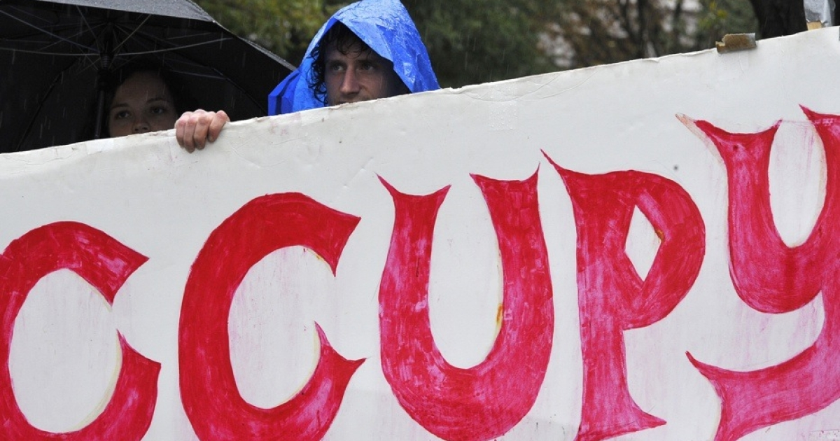 Protesters march under the heavy rain during an