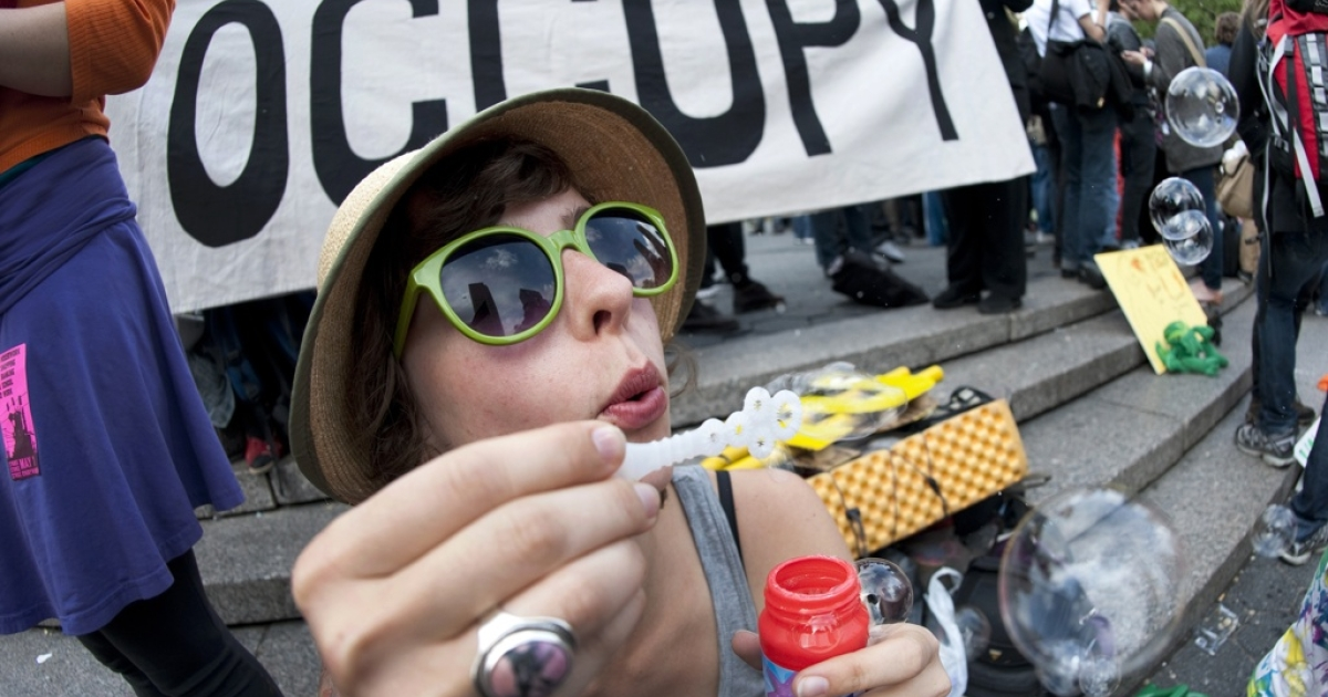 Katie, a college graduate, blows bubbles during an Occupy Wall Street rally against the high cost of college on April 25 in New York.</p>