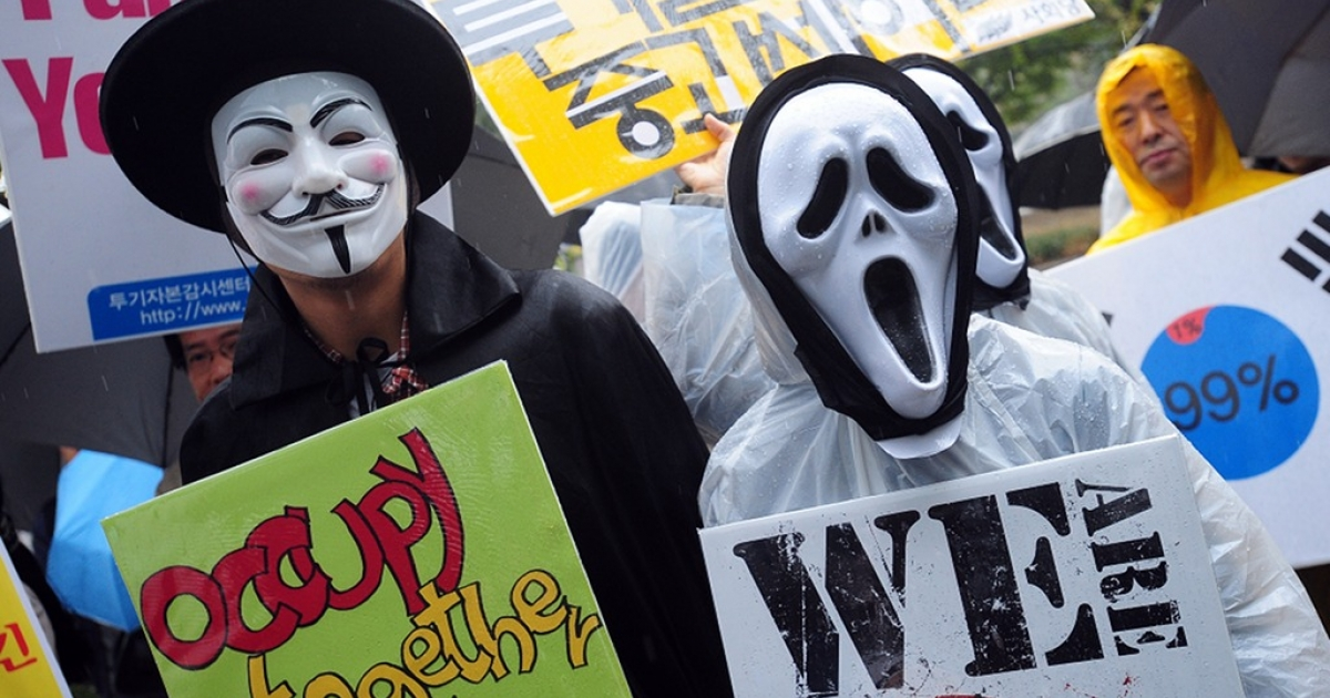 South Korean protesters wearing masks hold up banners during the 'Occupy Seoul' rally as part of the worldwide protest inspired by 'Occupy Wall Street' in Seoul on October 15, 2011.</p>
