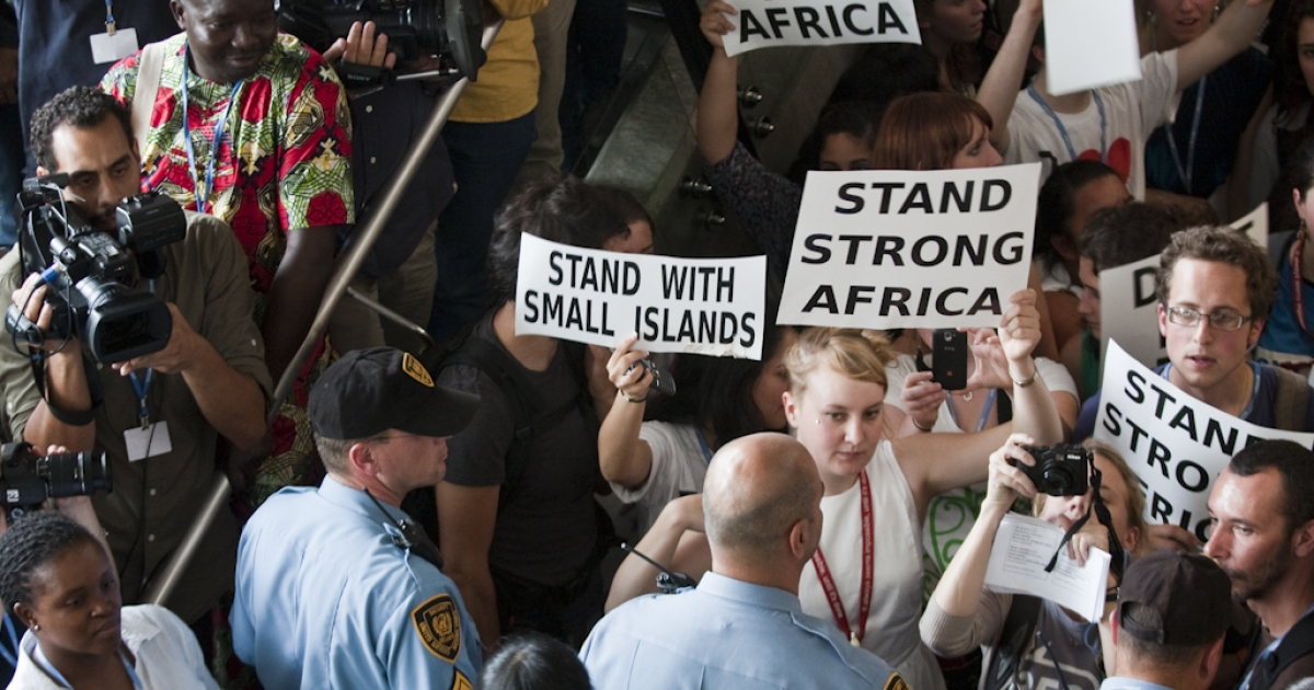 Protesters gather in a hall inside the Durban, South Africa conference center where the final day of UN climate change negotiations, known as COP 17, are being held, on December 9, 2011.</p>