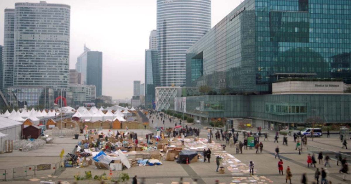 Workers walk past the French 'Indignants' camp out at Paris' La Defense business district early on November 15, 2011.</p>