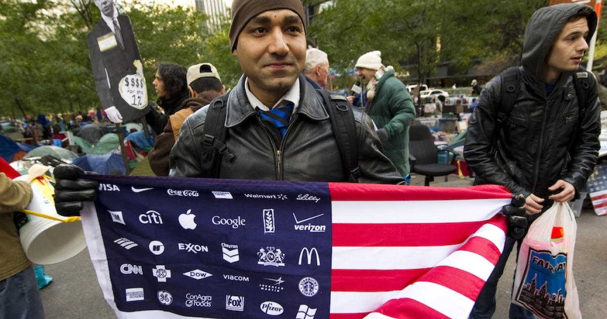 An Occupy Wall Street protester holds up an American flag with corporate logos replacing the stars on Nov. 1, 2011, in New York.</p>