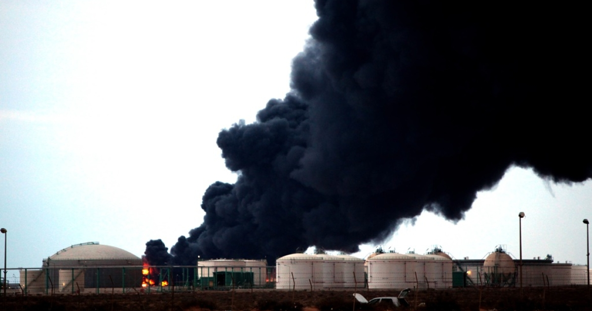 Smoke billows from a petrochemical factory following clashes between pro and anti-Gaddafi militants close to the eastern Libyan oil town of Ras Lanuf on March 12, 2011.</p>