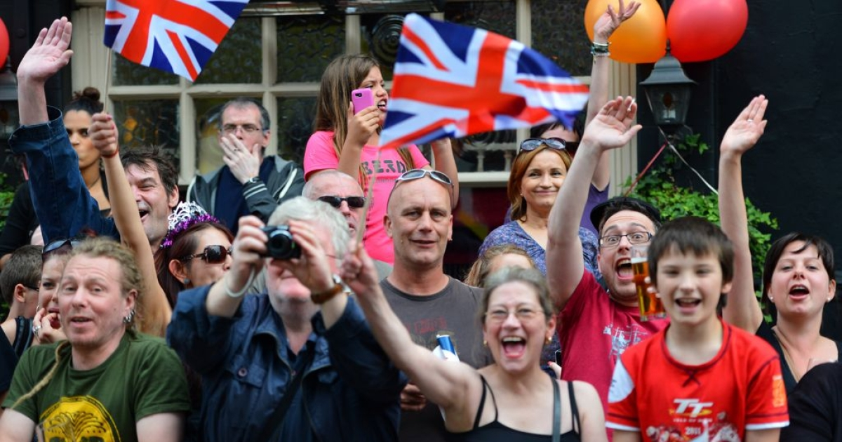 Crowds cheer as the Olympic Torch passes through the streets of Hackney, north London, on July 21, 2012.</p>