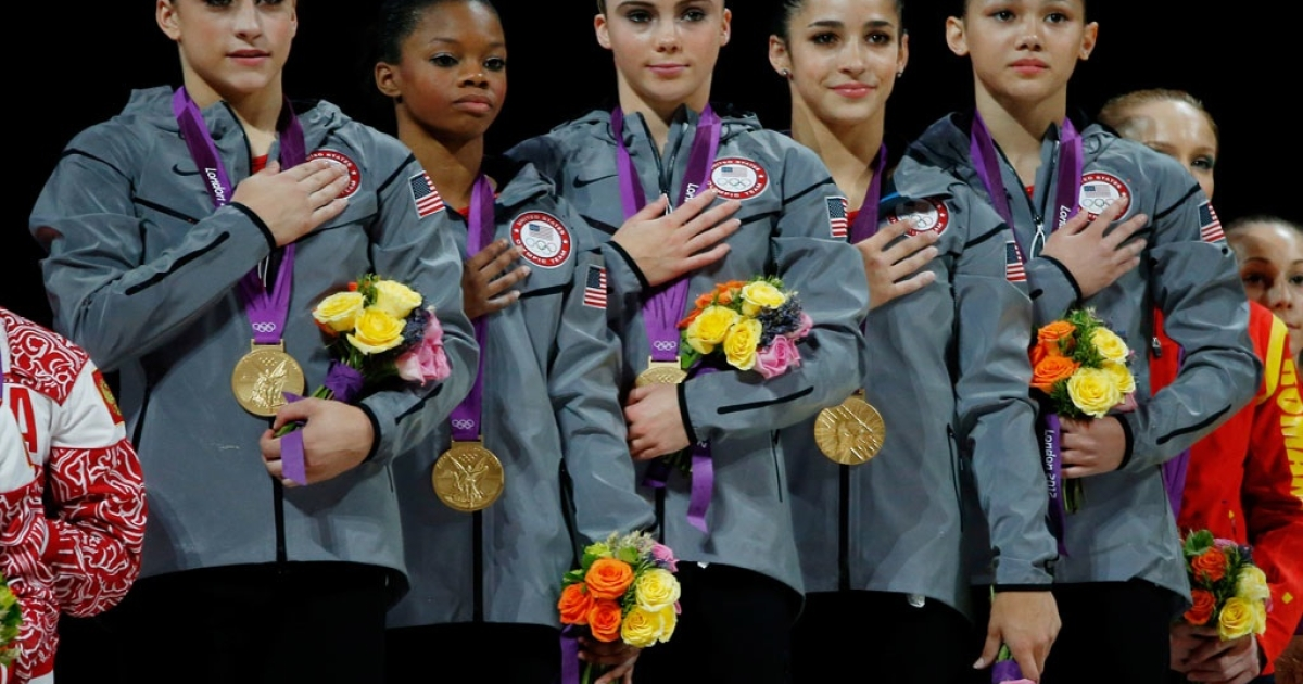 Jordyn Wieber, Gabrielle Douglas, Mc Kayla Maroney, Alexandra Raisman and Kyla Ross of the United States celebrate on the podium after winning the gold medal in the Artistic Gymnastics Women's Team final on Day 4 of the London 2012 Olympic Games at North Greenwich Arena on July 31, 2012 in London, England.</p>