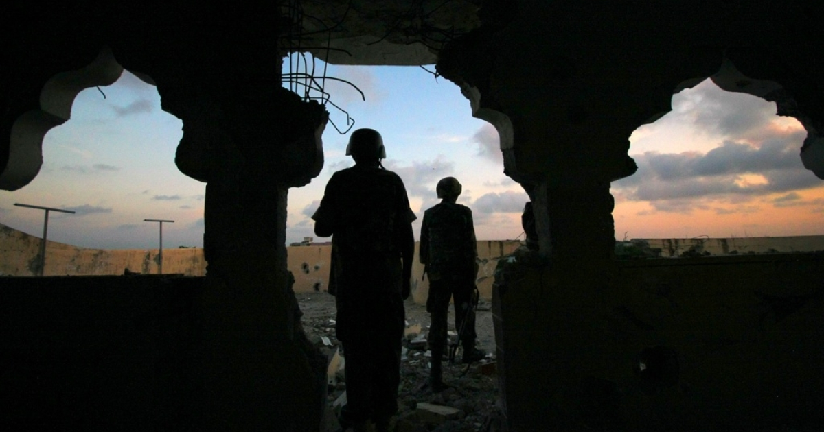 Uganda soldiers serving with the African Union Mission in Somalia (Amisom) 33rd Battalion are silhouetted against the Mogadishu skyline at sundown atop a partially destroyed building in the Yaaqshiid District of Mogadishu, where Amisom forces have pushed Al Shabaab militants beyond the city's northern fringes to the outskirts of the Somalia seaside capital. This picture was taken on November 22, 2011.</p>