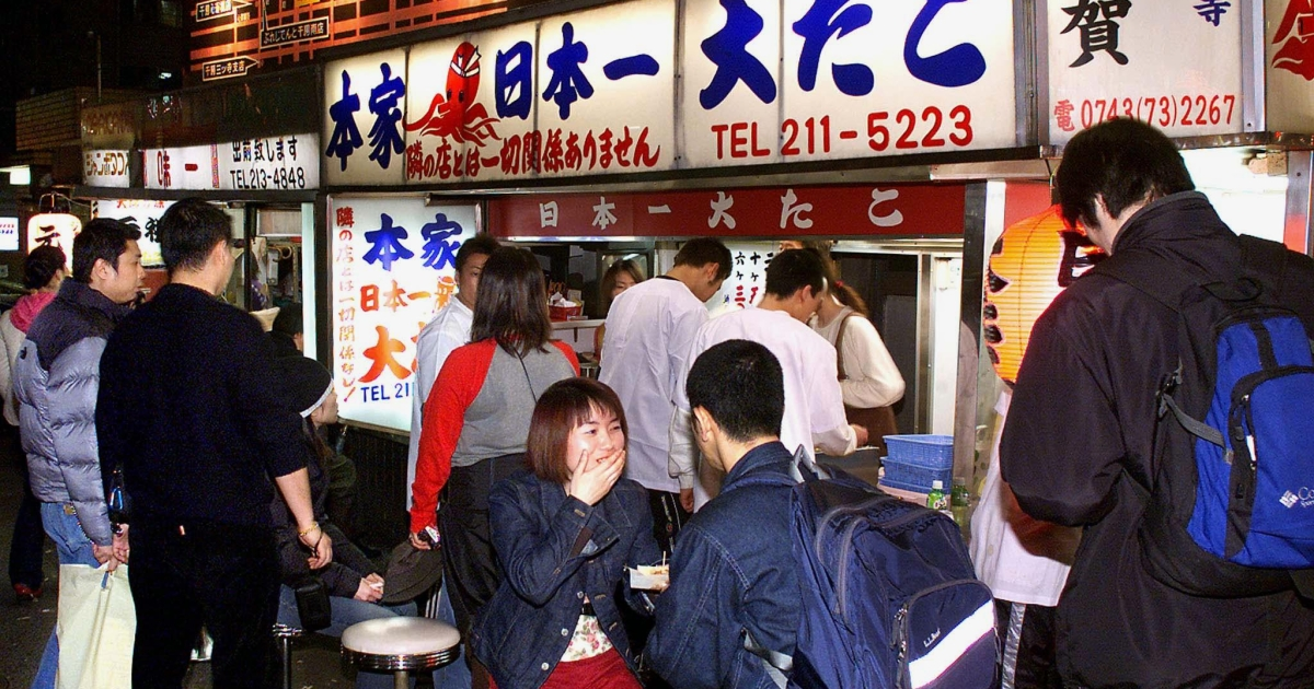 Local residents eat takoyaki, Osaka's famous junk food, at a street stall.</p>