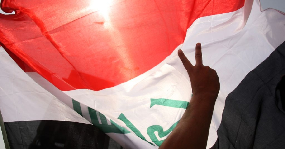 An Iraqi demonstrator makes the victory sign as he waves his national flag during a weekly protest against corruption, unemployment and poor public services at Baghdad's Tahrir Square on April 29, 2011.</p>