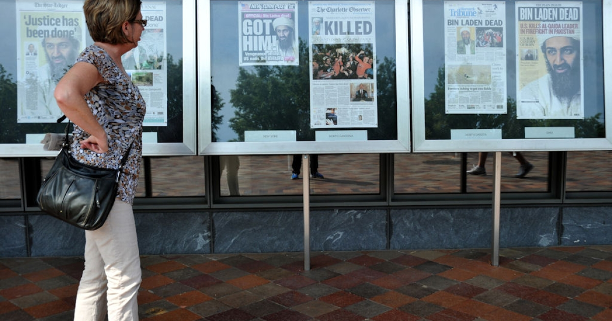 A woman looks at newspaper front pages announcing the death of Al Qaeda leader Osama bin Laden on May 2, 2011 in front of the Newseum in Washington, D.C.</p>