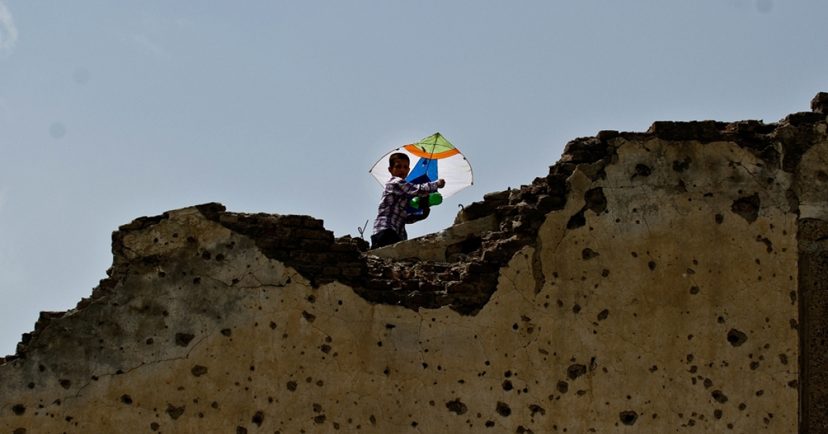 A young Afghan child flies a kite on top of the ruins of a building destroyed during war in Kabul on May 5, 2011.</p>
