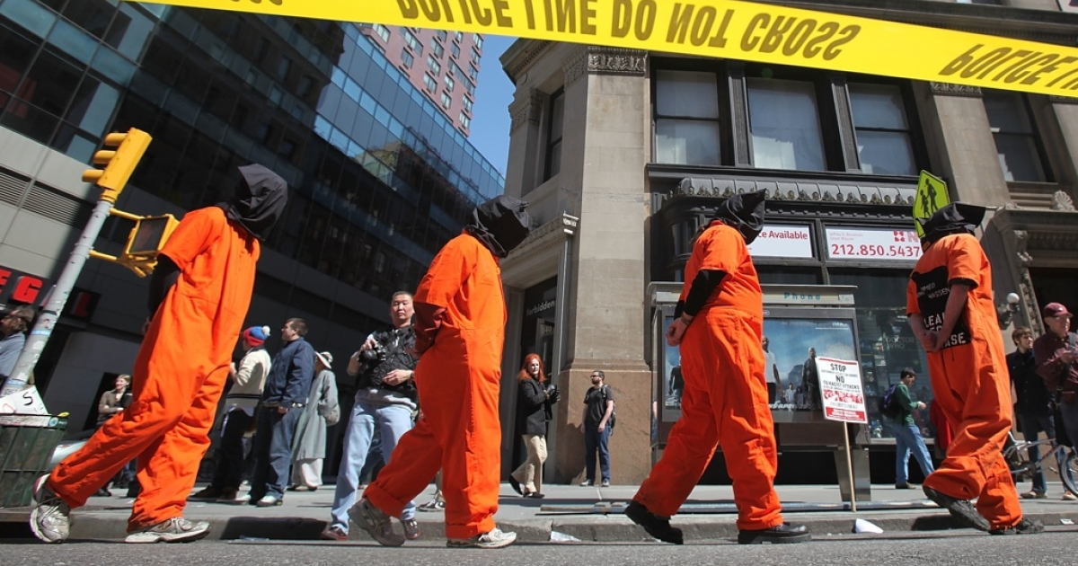 Protesters dressed as Guantanamo Bay prisoners march down Broadway during a large anti-war rally on April 9, 2011 in New York City.</p>