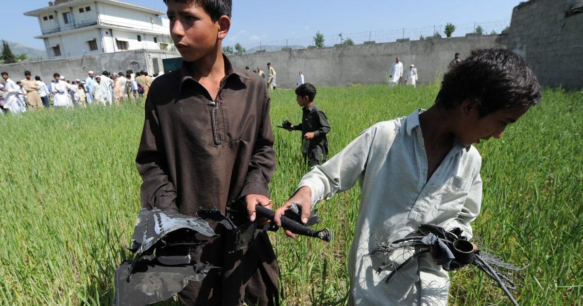 Pakistani boys collect debris at the site of the crashed helicopter outside the luxury compound that hid Al Qaeda leader Osama bin Laden in Abbottabad on May 3, 2011.</p>