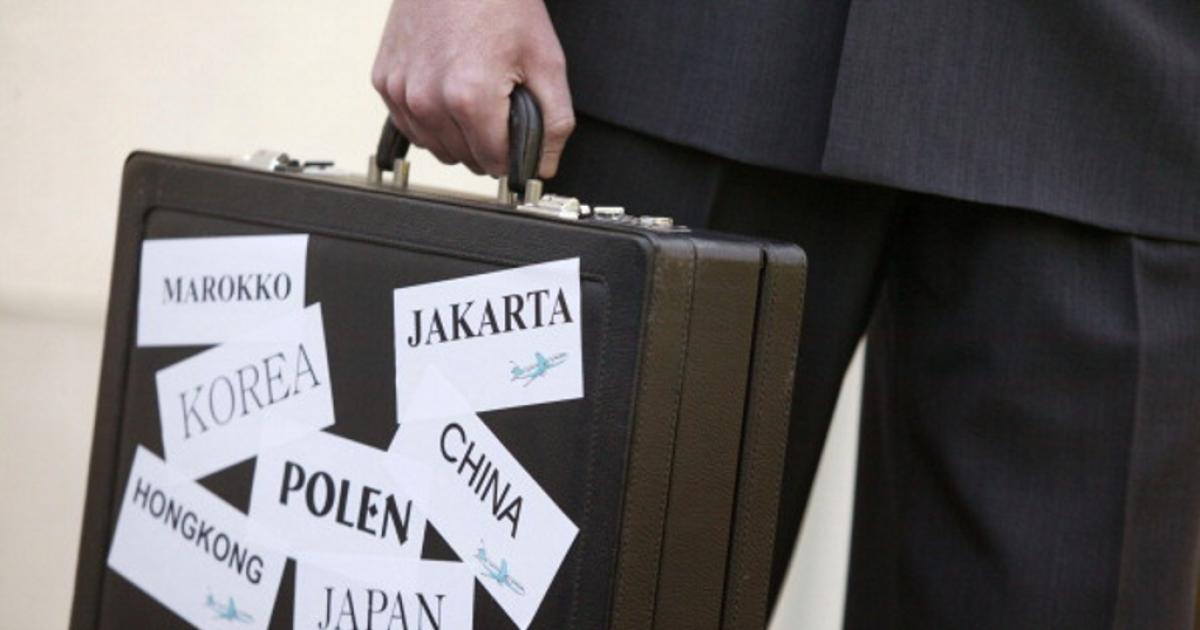 GERMANY - Man holding an attache case with the names of Marokko, Korea, HongKong, Poland, Japan, China, Jakarta.</p>