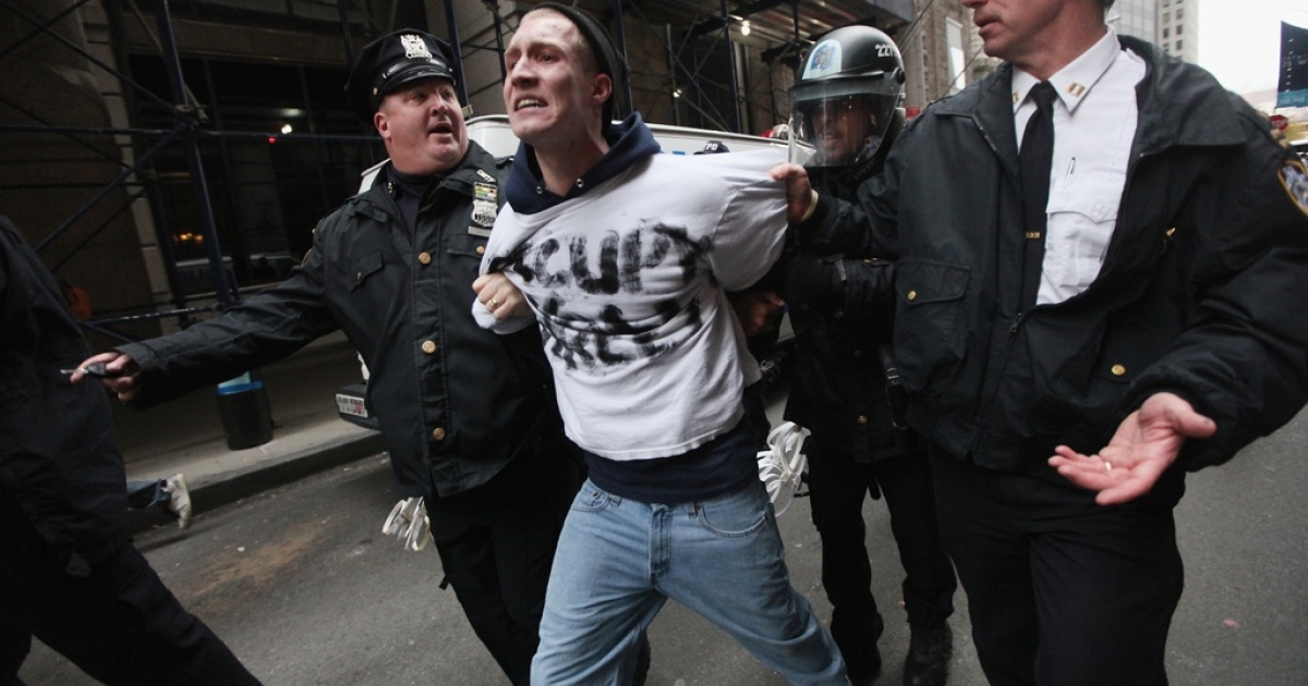 Occupy Wall Street protester Henry Cames is arrested by police a few blocks away from the New York Stock Exchange on Nov. 17, 2011, in New York City. Hundreds of protesters attempted to shut down the New York Stock Exchange today, blocking roads and tying up traffic in Lower Manhattan.</p>