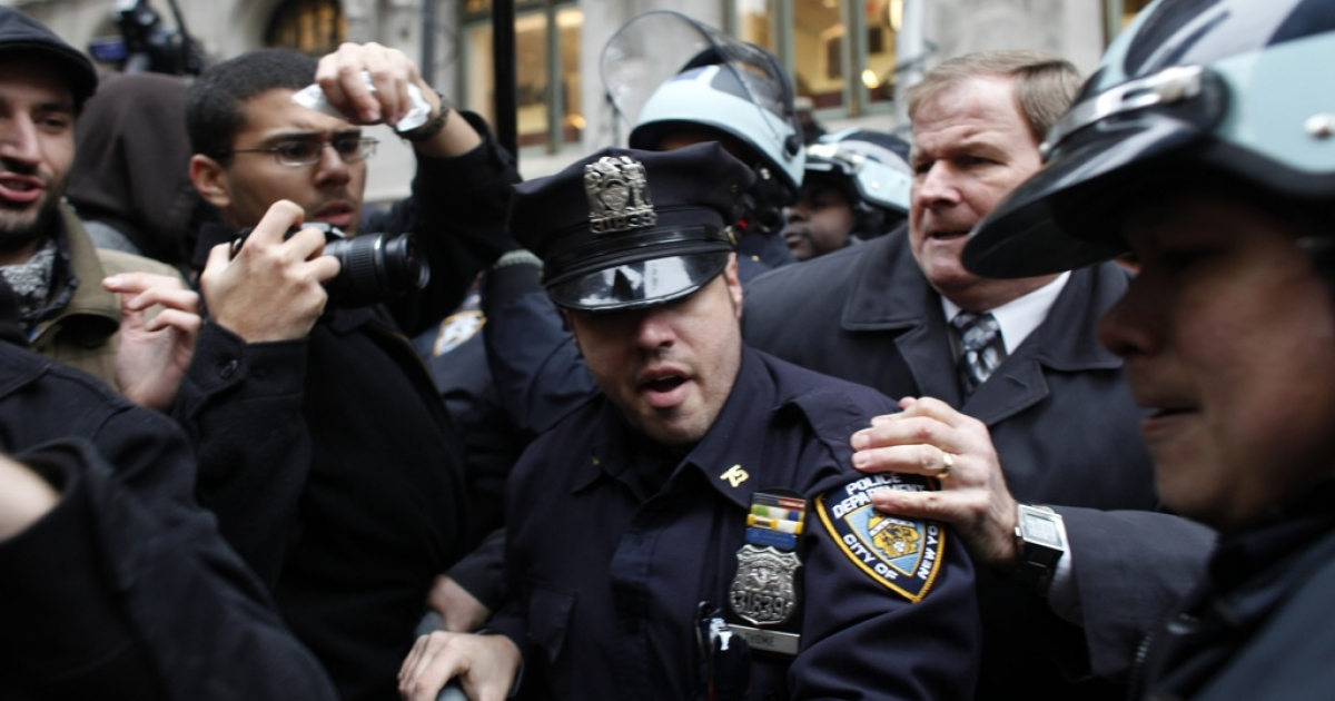 A protester affiliated with Occupy Wall Street is arrested a few blocks away from the New York Stock Exchange on Nov. 17, 2011, in New York City.</p>