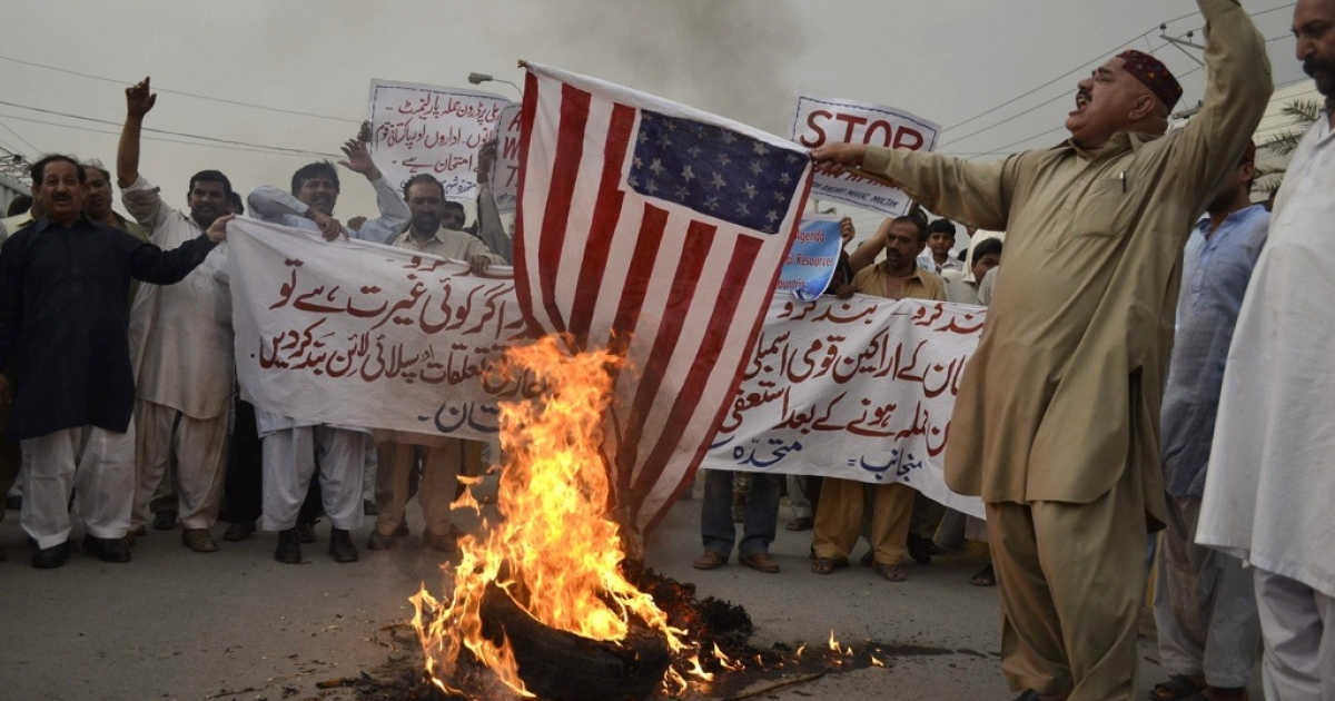 Pakistanis set fire to a U.S. flag during a protest in Multan on May 21, 2011.</p>