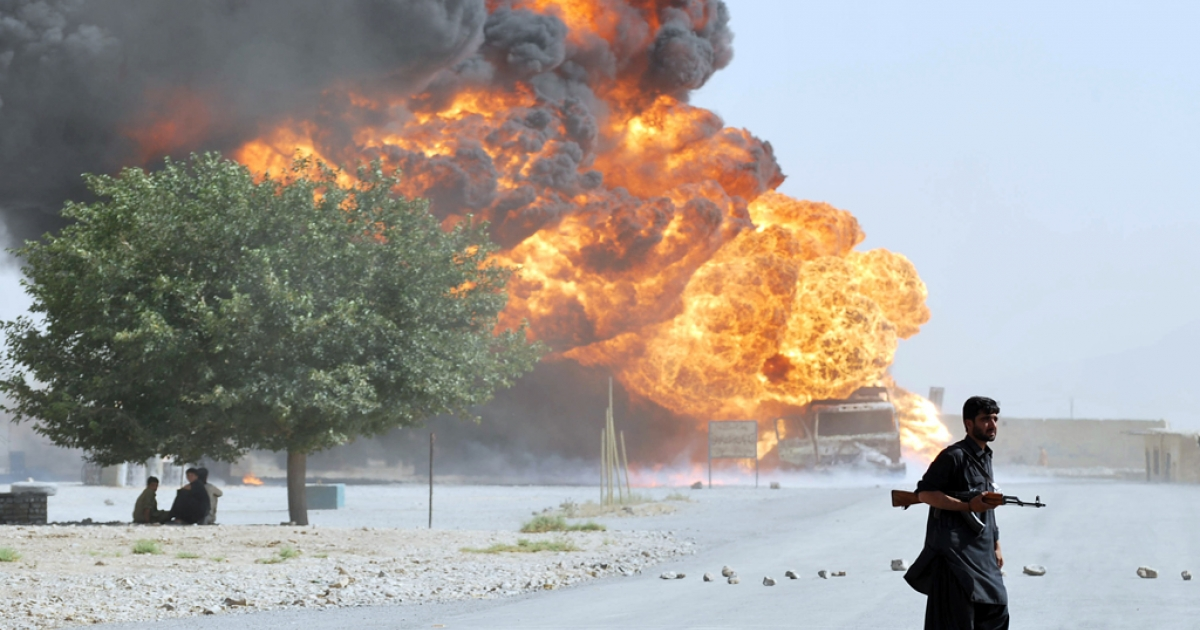 A Pakistani security personnel stands guard near a burning NATO oil tanker on the outskirts of Quetta on August 3, 2011. According to an official, two NATO oil tankers carrying logistic for ISAF forces from Karachi combusted after the vehicles where intercepted by armed men and fired upon.</p>