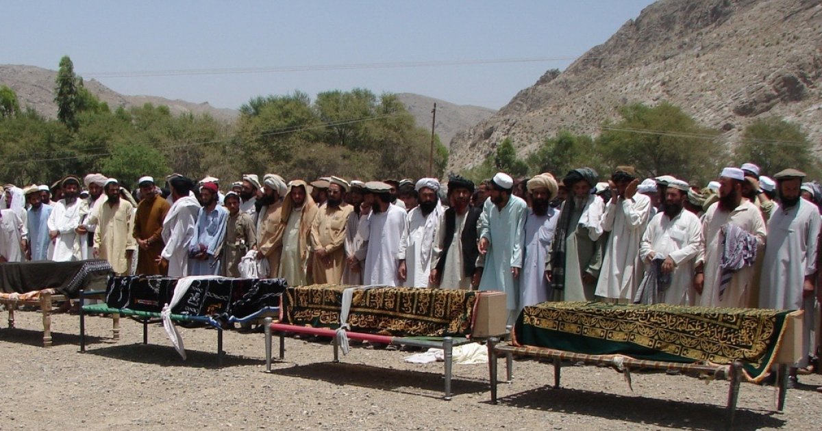 Pakistani tribesmen gather for funeral prayers before the coffins of people killed in a U.S. drone attack on June 15 in North Waziristan</p>