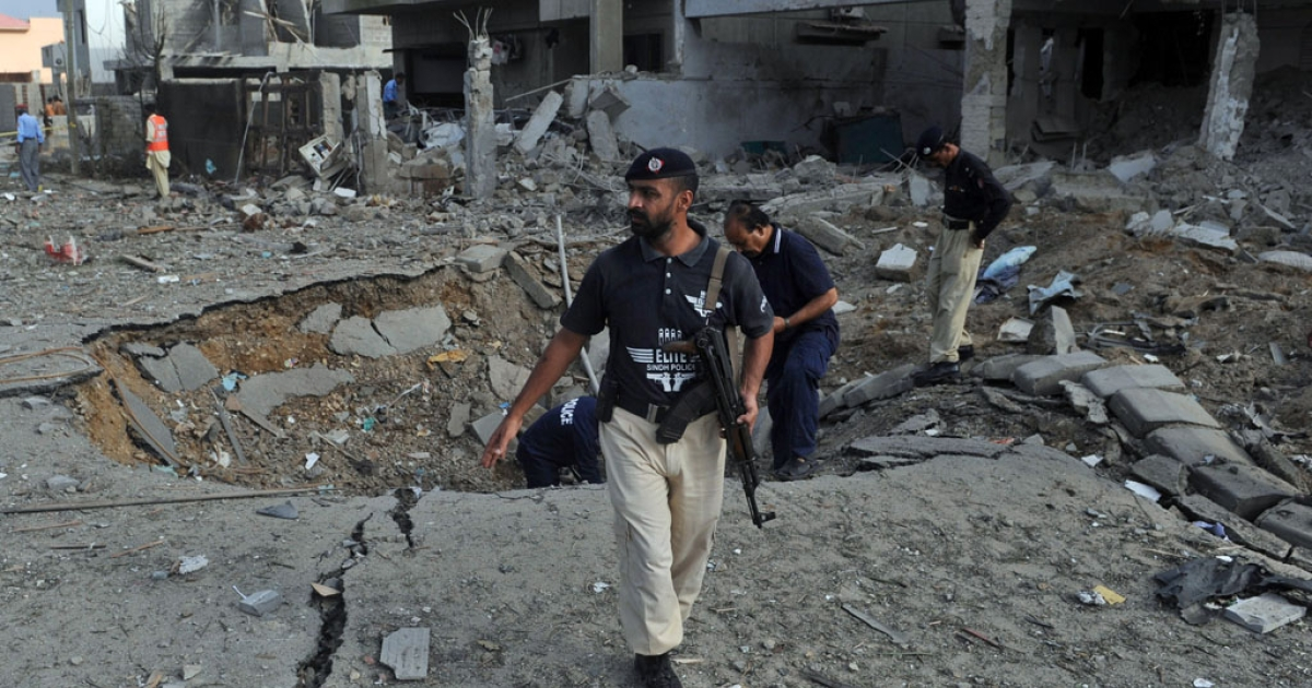 Pakistani investigators inspect the crater caused by a bomb blast in Karachi on Sept. 19, 2011.</p>
