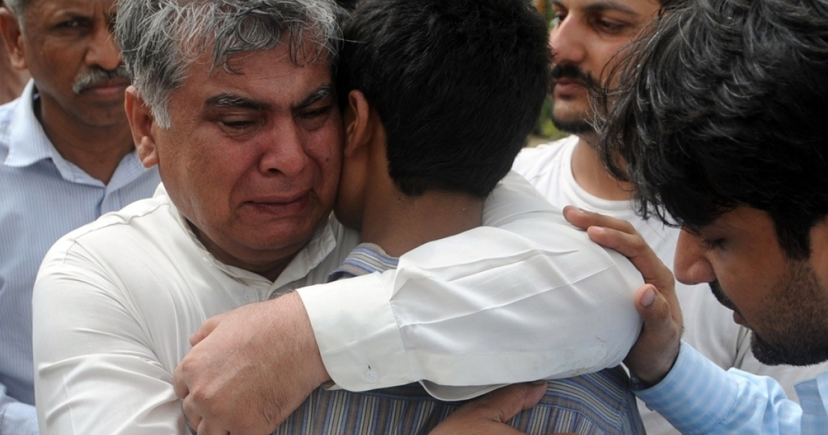 Mourners comfort Fahad Saleem, son of Pakistani journalist Syed Saleem Shahzad, during the journalist's funeral ceremony in Karachi on June 1, 2011. Hundreds of mourners turned out for the burial of the Pakistani journalist who had said he was being threatened by the country's intelligence services before he was tortured to death.</p>
