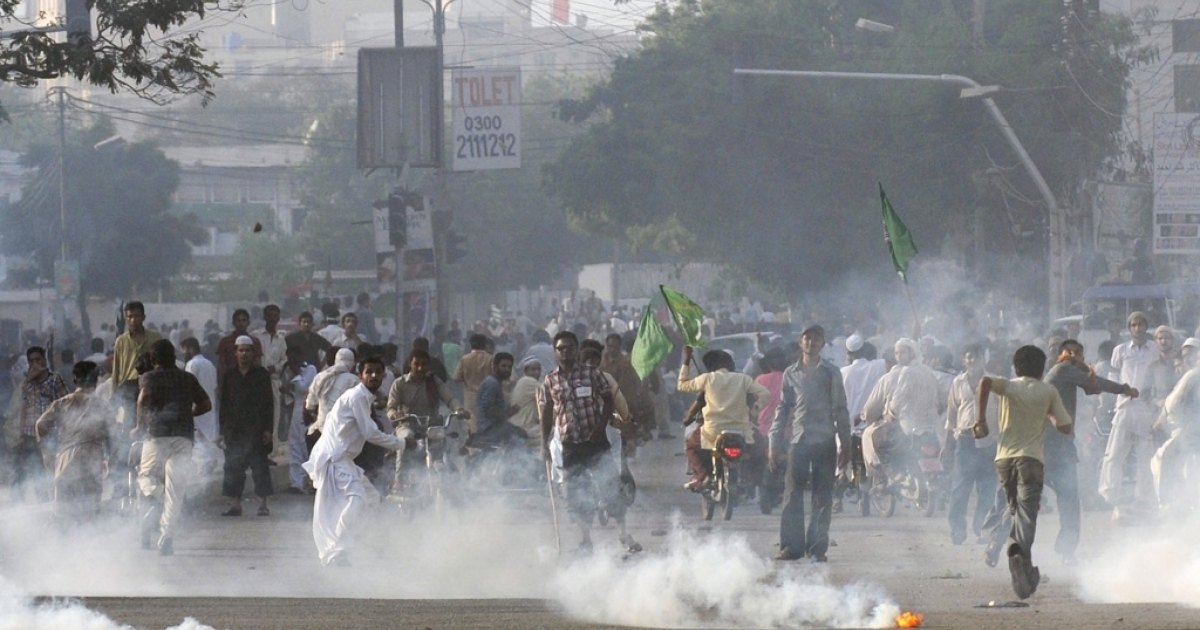 Pakistani demonstrators disperse after police fire tear gas in Karachi on Sept. 21, 2012.</p>